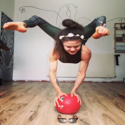 Girl puts shades on whilst balancing with her hands on a ball using just her feet